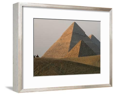 Camel Riders are Dwarfed by the Pyramids of Giza-James L^ Stanfield-Framed Art Print
