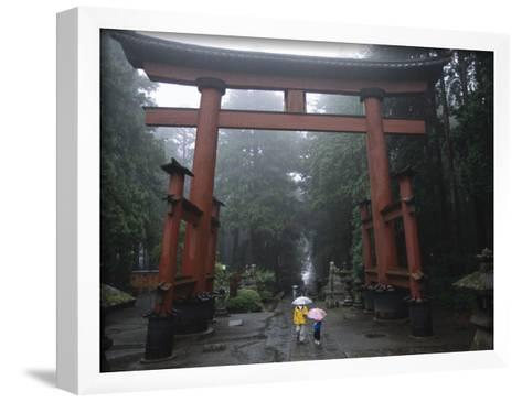 Tourists with Umbrellas Walk under an Arch at the Base of Mount Fuji-Karen Kasmauski-Framed Art Print