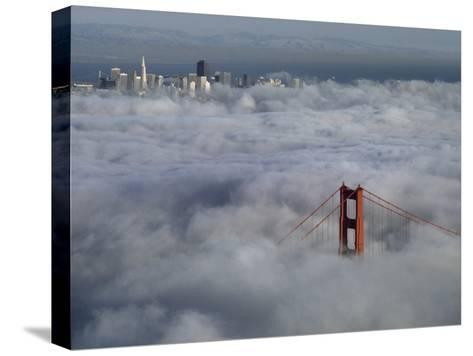 A Glowing Tower of the Golden Gate Bridge Rises Above the Fog-Jim Sugar-Stretched Canvas Print