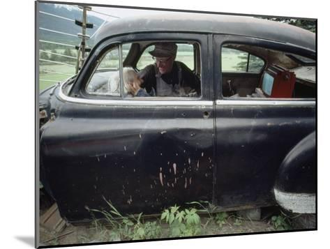 A Mother and Son Watch Television in an Old Car-Chris Johns-Mounted Photographic Print