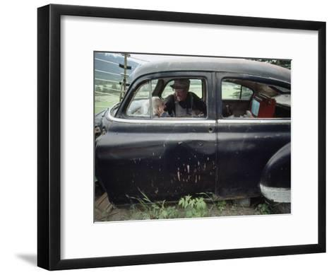 A Mother and Son Watch Television in an Old Car-Chris Johns-Framed Art Print