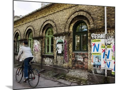 Cyclist in Freetown Christiania, with Anti European Union Posters on Wall-Christian Aslund-Mounted Photographic Print