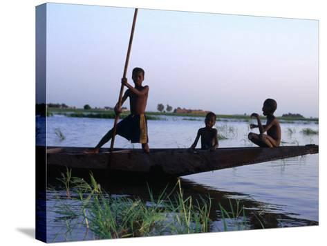Three Boys Play on a Canoe (Pirogue) on the River in Mopti-Dan Herrick-Stretched Canvas Print