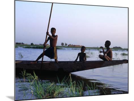 Three Boys Play on a Canoe (Pirogue) on the River in Mopti-Dan Herrick-Mounted Photographic Print