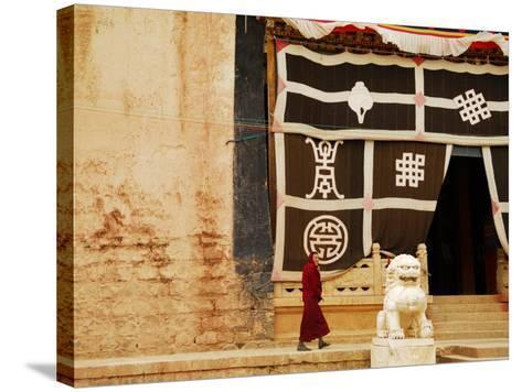 Smiling Monk Walking Towards Entrance to Ganden Sumtseling Gompa (Songzanlin Si) Monastery-Felix Hug-Stretched Canvas Print
