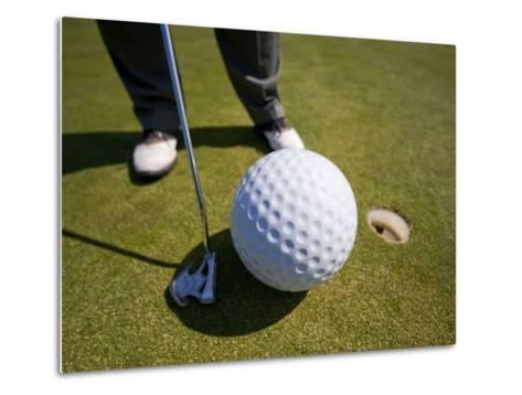 Man Playing Golf with Oversized Ball-Thomas Winz-Metal Print
