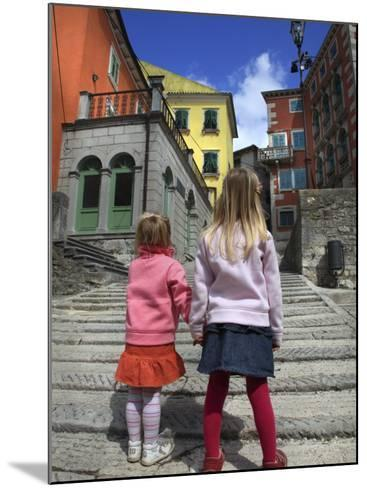 Two Girls on Ulica 1 Maja Street with Colourful Buildings-Ruth Eastham & Max Paoli-Mounted Photographic Print