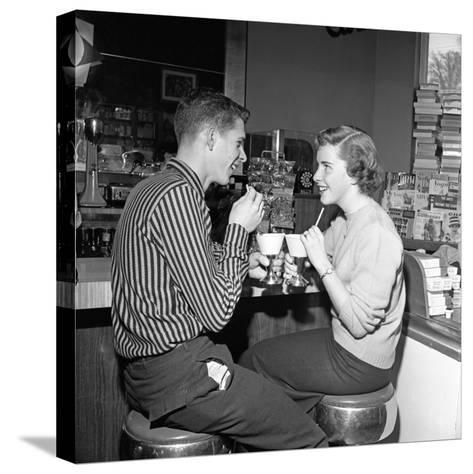 Teen Couple on Stools at Soda Fountain Drinking Shakes and Smiling at Each Other-H^ Armstrong Roberts-Stretched Canvas Print