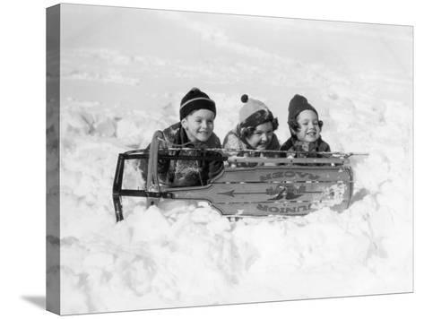 Two Girls and One Boy Lying on Belly in Snow Using Sled As Shield-H^ Armstrong Roberts-Stretched Canvas Print