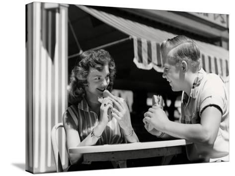 Teenage Couple Eating Hotdogs Outside at Refreshment Stand Table-H^ Armstrong Roberts-Stretched Canvas Print