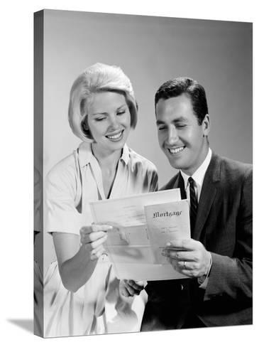 Husband and Wife Homeowners Looking at Mortgage and Smiling-H^ Armstrong Roberts-Stretched Canvas Print