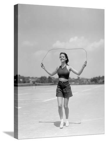 Smiling Teenage Woman Jumping Rope For Exercise Wearing Shorts and Polka Dot Halter Top-H^ Armstrong Roberts-Stretched Canvas Print