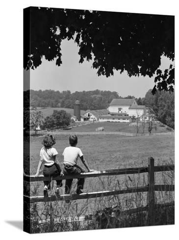 Boy and Girl Sitting on Fence, Overlooking Farm Fields-H^ Armstrong Roberts-Stretched Canvas Print