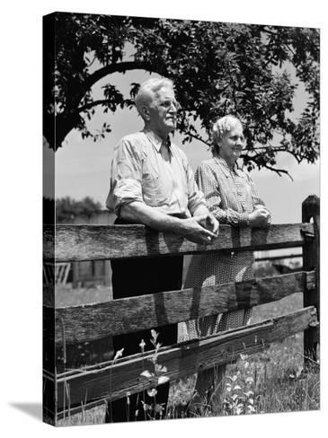 Elderly Couple on Farm Standing at Wooden Fence Looking Off Into Distance-H^ Armstrong Roberts-Stretched Canvas Print
