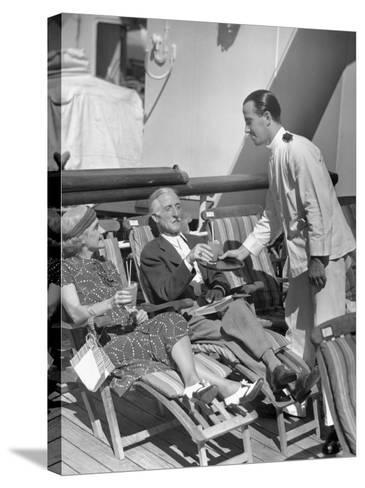 Elderly Couple Being Served Drinks on Deck of Cruise Ship-George Marks-Stretched Canvas Print