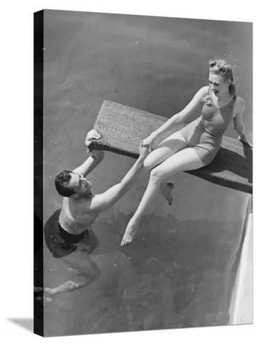 Woman Sitting on Diving Board, Man Grasping Her Hand-George Marks-Stretched Canvas Print