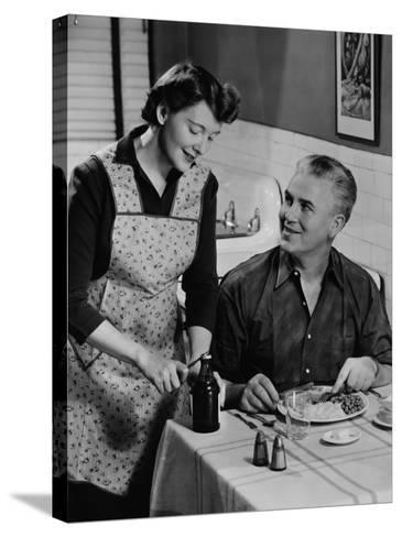 Woman Opening Beer Bottle For Man Eating Dinner-George Marks-Stretched Canvas Print