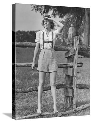 Barefoot Woman in Shorts Standing on Wooden Fence on Meadow-George Marks-Stretched Canvas Print