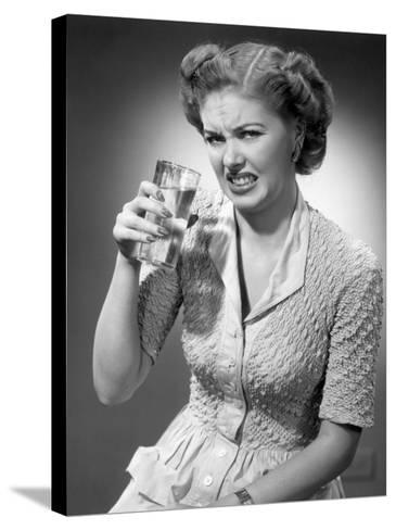 Woman Drinking Glass of Water With Look of Disgust-George Marks-Stretched Canvas Print