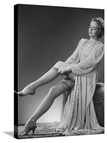 Young Woman Putting on Stockings in Studio-George Marks-Stretched Canvas Print
