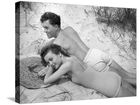 Young Couple in Bathing Suits Lying on Sand-George Marks-Stretched Canvas Print