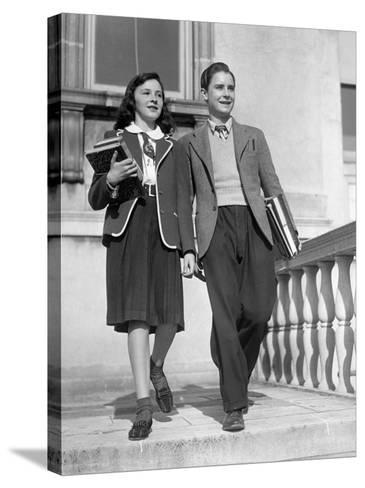 Teen Couple With Books Walking Outside School-George Marks-Stretched Canvas Print