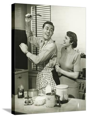 Young Cheerful Couple in Kitchen, Man in Apron-George Marks-Stretched Canvas Print