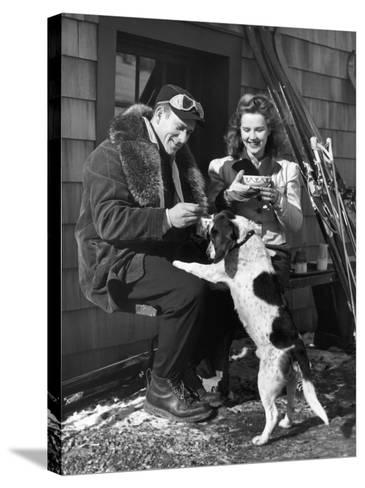 Couple With Dog in Front of Ski Lodge-George Marks-Stretched Canvas Print