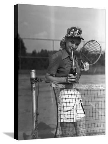 Woman Drinking Cola at Tennis Net-George Marks-Stretched Canvas Print