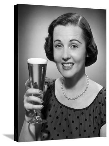Woman Raising a Glass of Beer-George Marks-Stretched Canvas Print