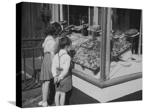 Boy and Girl Looking in at Bakery Window--Stretched Canvas Print