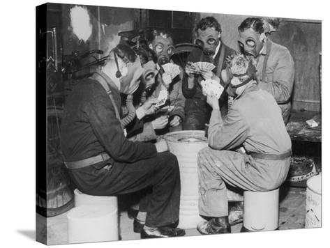 Group of Men Playing Cards, Wearing Gas Masks--Stretched Canvas Print
