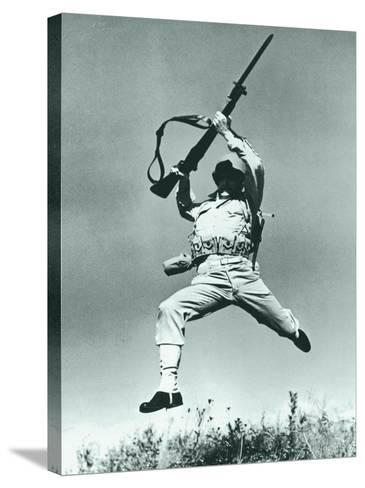 Soldier Jumping With Rifle, Low Angle View--Stretched Canvas Print