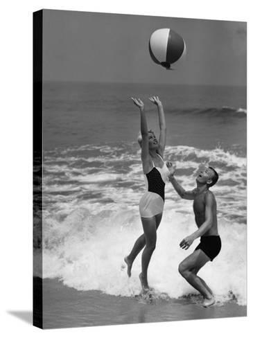 Young Couple Playing With Beach Ball at Water's Edge--Stretched Canvas Print