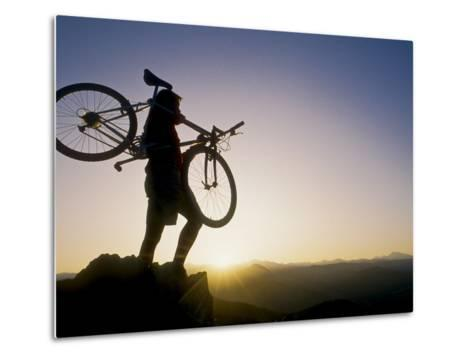 Silhouette of Mountain Biker at the Summit During Sunrise--Metal Print
