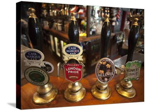 England, London, Beer Pump Handles at the Bar Inside Tradional Pub-Steve Vidler-Stretched Canvas Print
