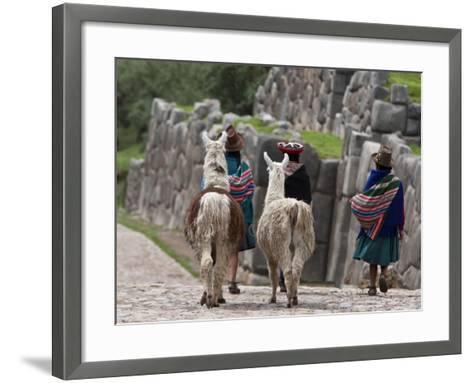 Peru, Native Indian Women Lead their Llamas Past the Ruins of Saqsaywaman-Nigel Pavitt-Framed Art Print