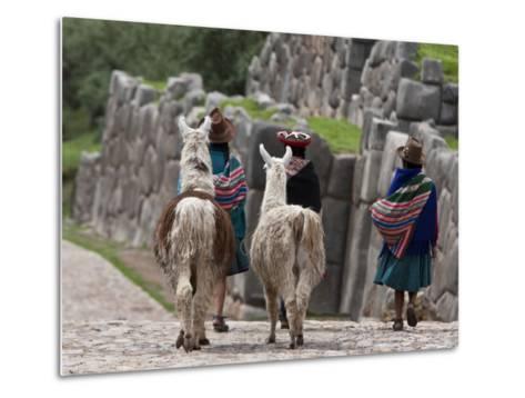 Peru, Native Indian Women Lead their Llamas Past the Ruins of Saqsaywaman-Nigel Pavitt-Metal Print