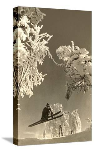 Airborne Skier Amid Frost-Laden Trees--Stretched Canvas Print