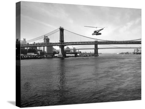 NYC Police Helicopter Hovering over the East River Next to the Manhattan Bridge--Stretched Canvas Print