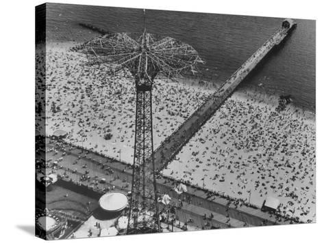 The Beach at Coney Island Looking Through Parachute Drop Tower at Crowded Beach--Stretched Canvas Print