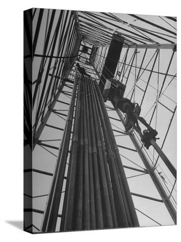 Vertical View of Oil Rig Showing Stacked Drill Pipes and Derrick Man at Work--Stretched Canvas Print