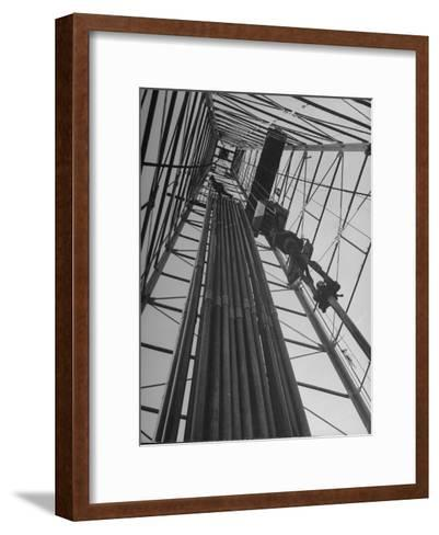 Vertical View of Oil Rig Showing Stacked Drill Pipes and Derrick Man at Work--Framed Art Print