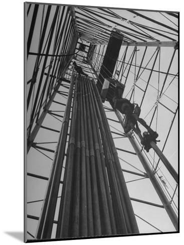 Vertical View of Oil Rig Showing Stacked Drill Pipes and Derrick Man at Work--Mounted Photographic Print