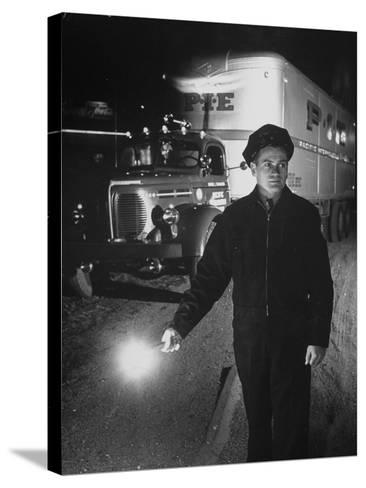 The Driver Placing a Flare on the Dark Road Where the Truck Is Stalled--Stretched Canvas Print