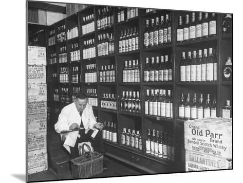 Steward at the Waldorf Astoria Hotel Working in Room Containing Wine and Spirits--Mounted Photographic Print