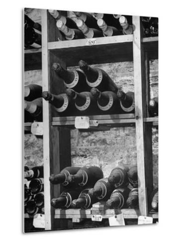 Dust Covered French Vintage Champagnes Lying on Racks in the Wine Cellar--Metal Print