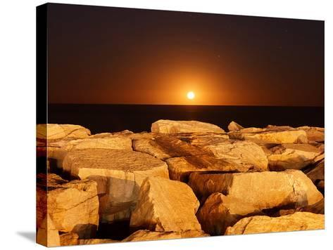 The Moon Rising Behind Rocks Lit by a Nearby Fire in Miramar, Argentina-Stocktrek Images-Stretched Canvas Print