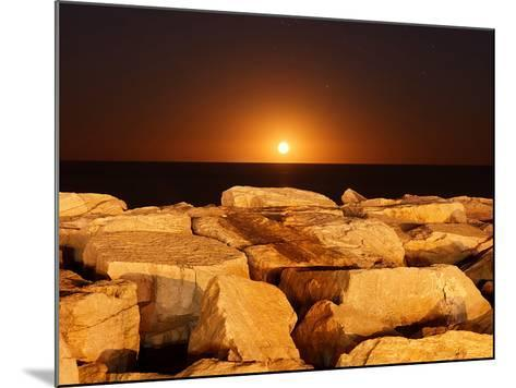 The Moon Rising Behind Rocks Lit by a Nearby Fire in Miramar, Argentina-Stocktrek Images-Mounted Photographic Print