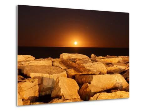 The Moon Rising Behind Rocks Lit by a Nearby Fire in Miramar, Argentina-Stocktrek Images-Metal Print